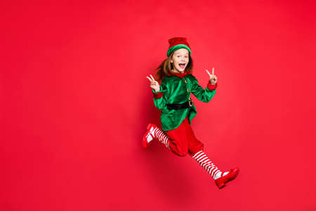 Full length of elf having fun showing v-sign isolated over bright vivid shine red background