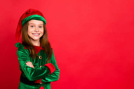 Portrait of cheerful elf kid with her hands crossed smiling ready to help in christmas night wearing green hat fantasy costume isolated over red background