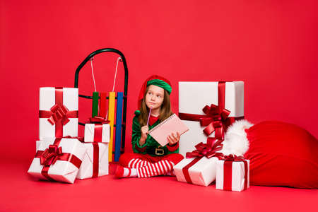 Nice attractive dreamy bewildered pensive funny pre-teen elf writing winter holly jolly miracle tradition idea wish want expect to do list isolated over bright vivid shine red background Stock Photo