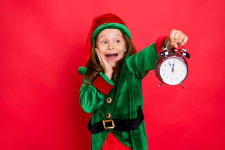 Close-up portrait of cheerful pre-teen elf holding clock isolated over red background