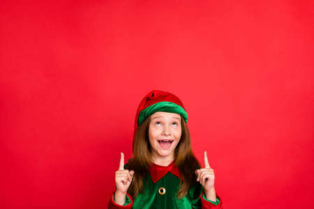 Portrait of impressed elf child in hat cap screaming wow omg showing adverts with her index finger isolated over red background
