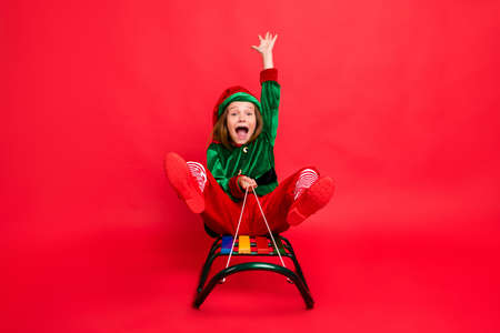 Portrait of her she nice attractive lovely funny charming cheerful cheery glad carefree pre-teen elf santa claus having fun sledging fairy tale miracle isolated over bright vivid shine red background