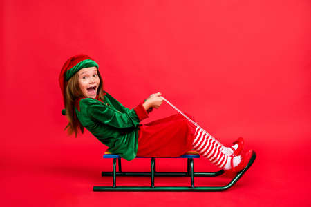Full size profile side photo of crazy elf in green cap with red long hairstyle screaming sledding wearing elf costume isolated over red background
