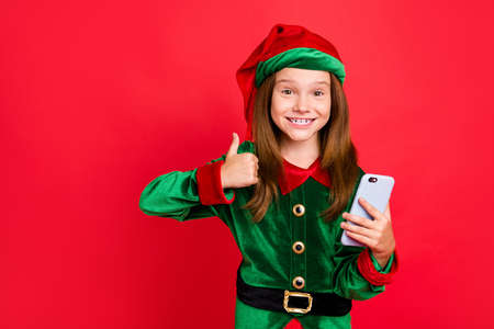 Portrait of cheerful schoolkid with long red head haircut showing thumb up holding gadget wearing green hat headwear cap costume isolated over red background