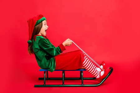 Full length profile side photo of excited elf kid in hat with long red head haircut sledding screaming wearing cap costume isolated over red background Standard-Bild - 130354978