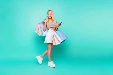 Full length body size view of nice attractive slim fit fashionable cheerful straight-haired girl carrying new cloth pleasure fast delivery isolated on bright vivid shine green turquoise background