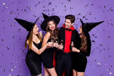Photo of witch ladies and wizard guy at halloween event drink golden wine clinking wineglasses wear black dresses caps suit and coat isolated purple color background