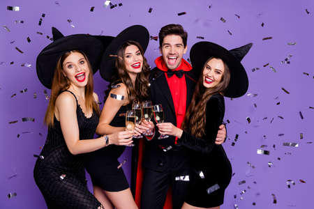 Photo of witch ladies and wizard guy at helloween event drink golden wine glitter flying in air wear black dresses caps suit and long coat isolated purple color background