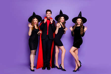Full body photo of four group people wizard guy and witch girlfriends playing evil roles biting scratching wear dresses caps and cloak isolated purple color background
