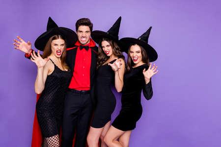 Foto de cuatro personas del grupo, tipo mago y novias brujas que juegan papeles malvados que van a morder el rasguño, usar vestidos cortos negros, gorras y manto aislado fondo de color púrpura Foto de archivo
