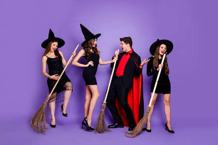 Full length photo of three witch ladies and warlock guy with brooms singing rocker songs chilling wear black dresses caps and long coat isolated purple color background