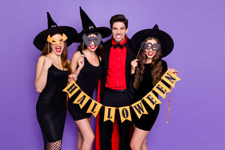 Boo. Terrifying. Portrait of dangerous creepy spooky group of people witches conjurer sorcerer hold ornament for october halloween event wear bat mask isolated over violet purple color background