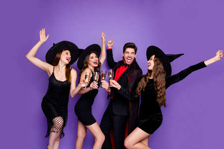 Photo of witch ladies and warlock guy chilling at halloween party drink golden wine raising arms up wear black dresses hats and vampire coat isolated purple color background Stock Photo