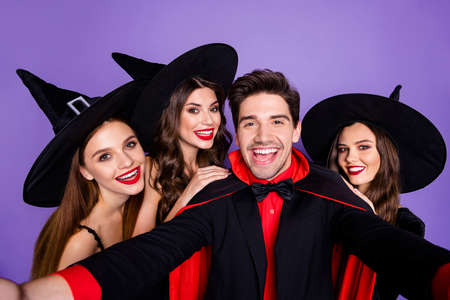 Close up photo of charming night mysterious dark creatures sorcerer and gorgeous witches lean shoulders take selfie enjoy october tradition event party isolated over violet purple color background