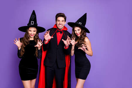 Retrato de criaturas misteriosas oscuras personas vampiro mago en capa y dos brujas rascan las manos dedos rugen verdaderos hechiceros en el tema de la fiesta de disfraces aislado sobre fondo de color violeta púrpura Foto de archivo