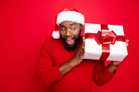 Close up photo of amazed student in xmas cap shaking package with ribbon for christmas screaming wow wearing pullover isolated over red background