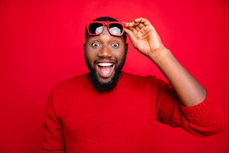 Portrait of impressed guy with eyewear eyeglasses screaming wow omg hear wonder winter season sales shopping discounts isolated over red background