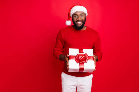 Portrait of cheerful student with santa claus cap holding package give present for noel wearing jumper pants trousers isolated over red background Stock Photo