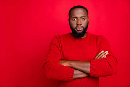 Portrait of minded guy looking with his hands crossed ready to prepare for midnight wearing pullover isolated over red background