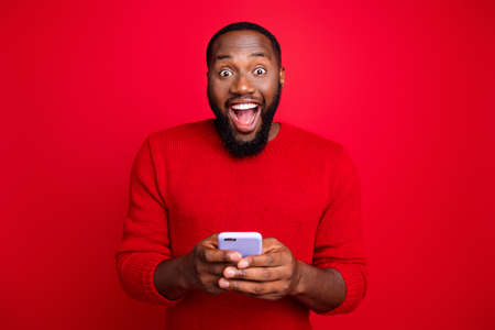 Close-up portrait of his he nice attractive cheerful cheery excited glad bearded guy using wireless connection wifi app 5g blog post smm fast speed isolated over bright vivid shine red background