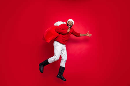 Full body profile side photo of cheerful guy in xmas santa claus hat holding carrying bag in christmas night wearing pullover pants trousers boot isolated over red background Stock fotó