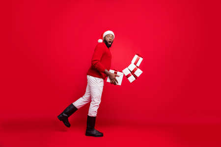 Full length profile side photo of upset freelancer in xmas cap stumbling with all package falling wearing stylish pullover pants isolated over red background