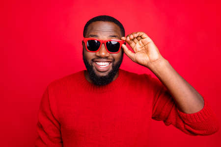 Close-up portrait of his he nice attractive cheerful cheery content cool bearded guy touching specs isolated over bright vivid shine red background Stock Photo