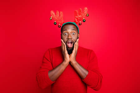 Portrait of astonished person in stupor touching his cheeks hear end of winter season shopping sales wearing deer costume stylish sweater isolated over red background