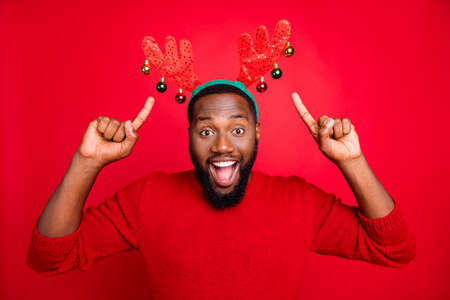 Theme night party concept. Portrait of astonished crazy man in stylish trendy pullover pointing at his deer toy costume recommending ads screaming wow omg isolated over red background Stock Photo