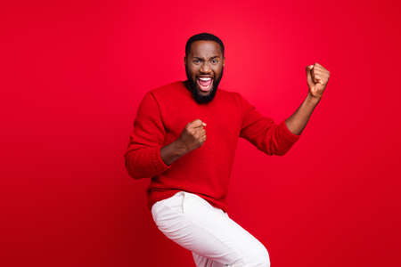 Portrait of his he nice attractive cheerful cheery satisfied glad bearded guy fan celebrating good news great accomplishment rejoicing isolated over bright vivid shine red background