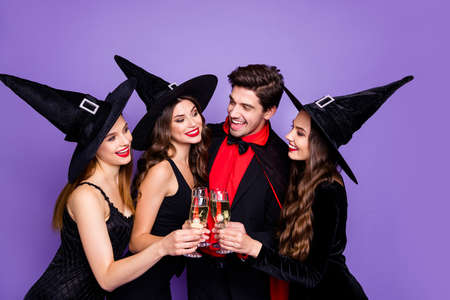 Foto de tres damas brujas emocionadas y un chico brujo escalofriante en la fiesta de halloween beber vino dorado usar vestidos negros sombreros y abrigo de vampiro aislado fondo de color púrpura Foto de archivo