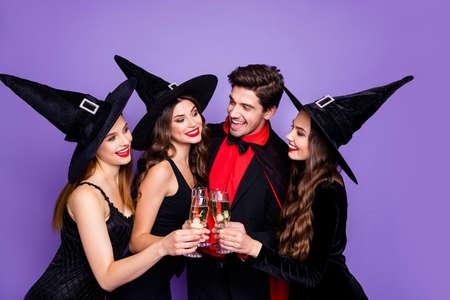 Foto di tre streghe eccitate e stregone che si rilassano alla festa di halloween bevono vino dorato indossano abiti neri cappelli e cappotto da vampiro sfondo di colore viola Archivio Fotografico