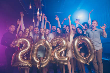 Leuke aantrekkelijke glamoureuze stijlvolle vrolijke positieve meisjes en jongens die plezier hebben met het in handen houden van grote grote aantallen feestelijke 2020-feeststemming in luxe nachtclub binnenshuis Stockfoto