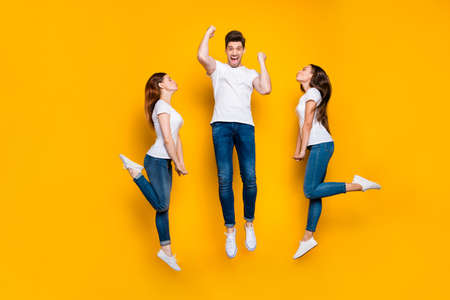 Full length body size view portrait of two nice attractive charming slim fit coquettish flirty cheerful cheery dreamy girls kissing one satisfied guy isolated over bright vivid shine yellow background Reklamní fotografie