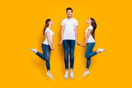 Full length body size view portrait of two nice attractive lovely lovable flirty cheerful cheery dreamy girls kissing one guy Valentine day isolated over bright vivid shine yellow background Reklamní fotografie