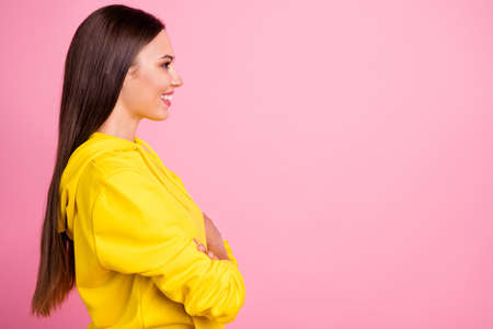 Photo of cheerful cute nice attractive girlfriend looking away to something standing in sport wear sweater yellow with arms crossed while isolated over pink pastel color background