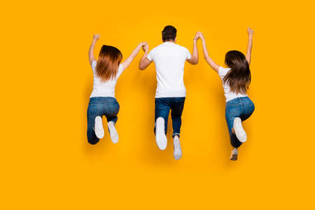 Rear back behind full length body size view of three nice attractive lovely slim sportive sporty person having fun free time isolated over bright vivid shine yellow background