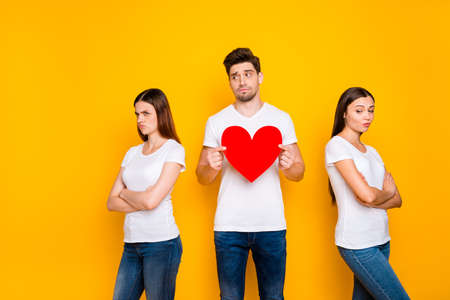 Portrait of one nice attractive doubtful guy holding in hands heart deciding between two offended girlfriends dilemma isolated over bright vivid shine yellow background Reklamní fotografie
