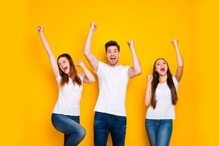 Retrato de tres agradable atractivo encantador alegre alegre persona celebrando logro fresco divirtiéndose levantando las manos aisladas sobre fondo amarillo brillante brillo vivo