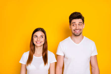 Portrait of charming buddies with long ginger foxy hair looking wearing white t-shirt isolated over yellow background 免版税图像