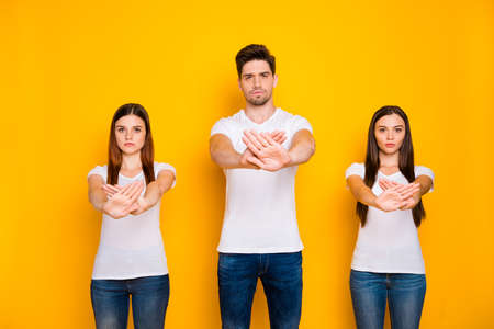 Portrait of strict mates crossing palms wearing white t-shirt denim jeans isolated over yellow background Stock Photo