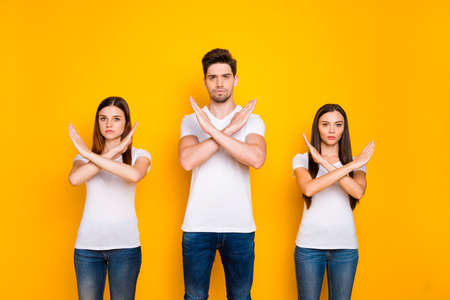 Portrait of strict youth crossing their hands wearing white t-shirt denim jeans isolated over yellow background Imagens