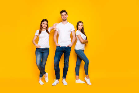 Full size photo of cool hipster with long hair folding their hands wearing white t-shirt denim jeans isolated over yellow background Stock Photo