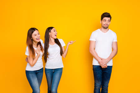 Portrait of excited girls mocking at guy standing shy wearing white t-shirt denim jeans isolated over yellow background