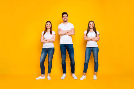 Full size photo of positive buddies with toothy smile crossing hands wearing white t-shirt isolated over yellow background Stock Photo