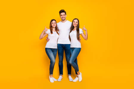 Full size photo of cheerful girls guy showing thumb up smiling wearing white t-shirt denim jeans isolated over yellow background