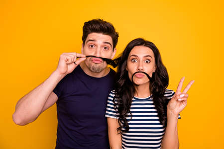 Photo of two fooling funky funny nice cute charming people husband and wife, pretending to have mustaches with girlfriend showing v-sign while isolated with yellow background