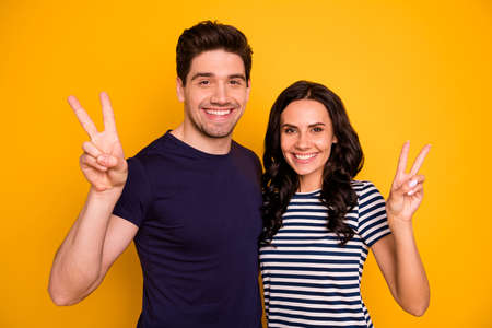 Close-up portrait of his he her she nice attractive lovely cheerful cheery, glad optimistic people married spouses showing v-sign holiday isolated over bright vivid shine yellow background Фото со стока
