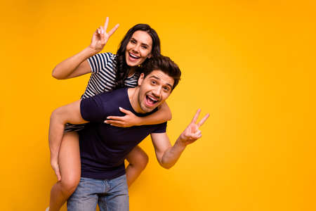 Photo of crazy nice cheerful couple of two people showing you v-sign while, isolated with yellow background