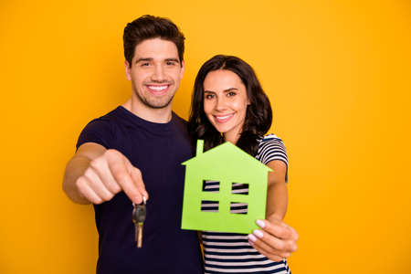 Photo of cheerful friendly couple of fallen in love offering you to buy new house, cheaply while isolated with yellow background